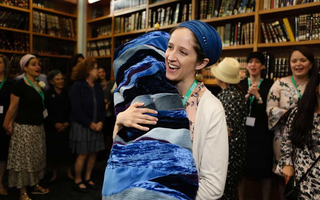 """הרבנית ג'ינה אנגלנדר רוקדת עם ספר תרה במהלך טקס סיום לימודיה בישיבת מהר""""ת בניו יורק, 17 ביוני 2019 (צילום: Shulamit Seidler-Feller/Maharat)"""