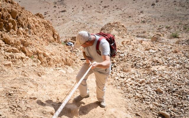 החוקר אורן גוטפלד יורד ממערה 52 באתר הארכיאולוגי בקומראן, 22 בינואר 2019 (צילום: לוק טרס/Times of Israel)
