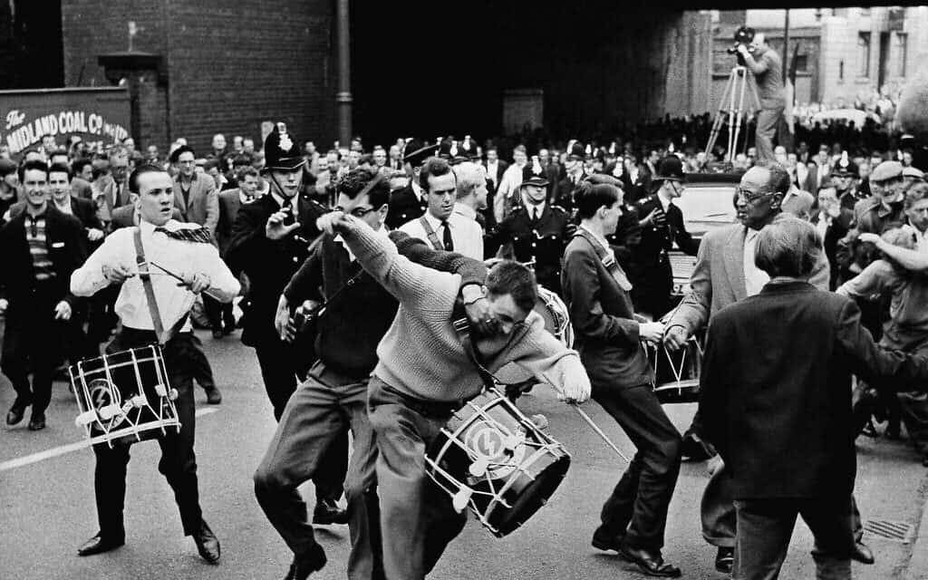 משקיף זועם תוקף את אחד המתופפים של מנהיג הפשיסטים בבריטניה, אוסוולד מוסלי, ראש תנועת האיחוד הימנית הקיצונית, במהלך צעדה במנצ'סטר, אנגליה, ב-29 ביולי 1962. אבנים ועגבניות הושלכו לעבר הצועדים לפני שהם הותקפו פיזית בידי הקהל (צילום: AP)