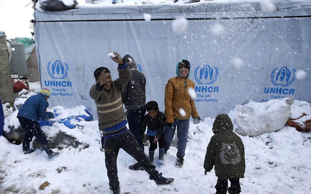 ילדים פליטים סורים משחקים בשלג בלבנון, ארכיון, 2017 (צילום: AP Photo/Hussein Malla)