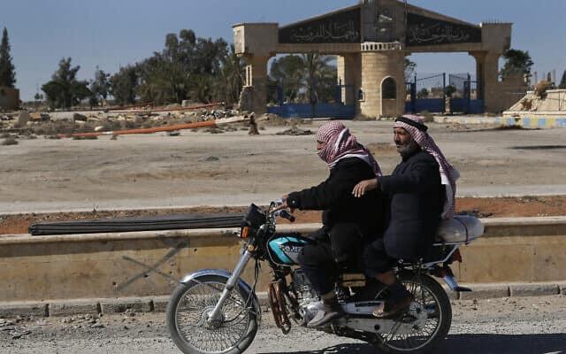 גברים סוריים חולפים ליד בית ספר מוסלמי שנהרס במלחמת האזרחים, 2018 (צילום: AP Photo/Hussein Malla))