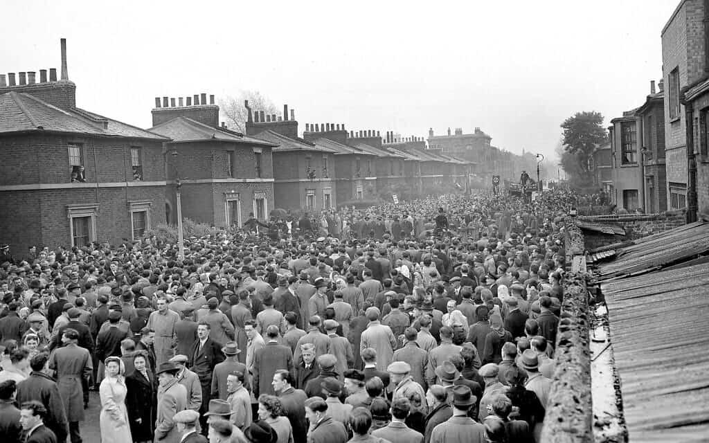 אוסוולד מוסלי, מנהיג הפשיסטים בבריטניה, עומד ברקע על מכונית השידור המסחרית שלו ומדבר במהלך צעדת 1 במאי באיסט אנד בלונדון, 1948 (צילום: AP)