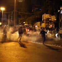 מפגינים בבירת לבנון ביירות, כשסביבם גז מדמיע שירתה המשטרה, ארכיון (צילום: Bilal Hussein, AP)