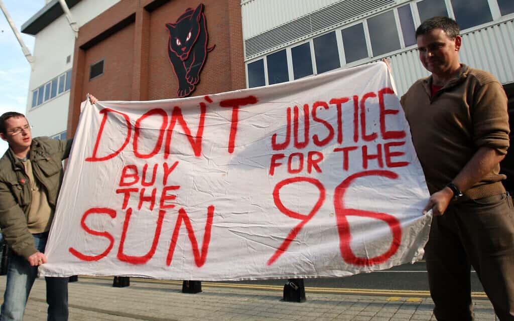 אוהדי ליברפול מחזיקים בשלט הקורא: ״צדק ל-96. אל תקנו את הסאן״ (צילום: AP Photo/Scott Heppell)