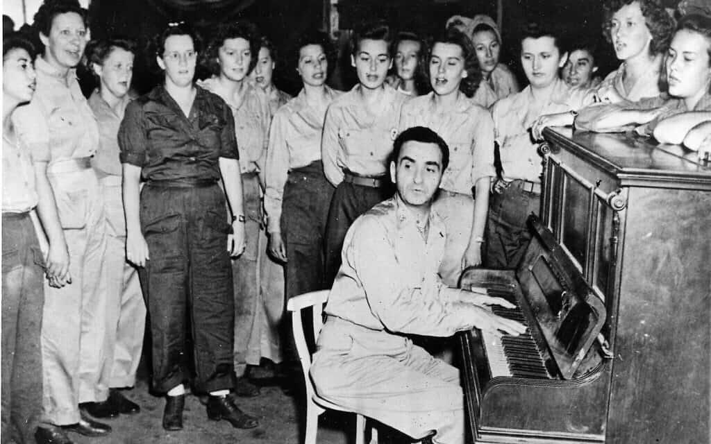 """אירווינג ברלין, כותב שירים, נגן פסנתר וזמר, מנגן את אחד משיריו מול חיילות בבסיס חייל האוויר של ארה""""ב במטה המזרח הרחוק בהולנדיה, גינאה החדשה ההולנדית, 31 בדצמבר, 1945 (צילום: AP\ צבא ארצות הברית)"""