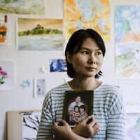 אשתו של שיווי וואנג, שהיה כלוא באירן מ-2016, אוחזת בתמונתו (צילום: Matt Rourke, AP)