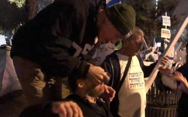 """פרופ' יורם יובל מעניק טיפול ראשוני לד""""ר מיכאל מוריס רייך שנפצע במאהל המחאה אמש על ידי אדם שהזדהה כליכודניק. צילום מתוך עמוד הפייסבוק של פרופ' יובל"""