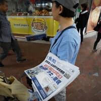 מוכר עיתונים עם כותרות על התפרצות סוג חדש של וירוס קורונה וחשש מהתפרצות מחודשת של וירוס ה-SARS, בעיר ווהאן שבהונג קונג (צילום: AP Photo/Andy Wong)