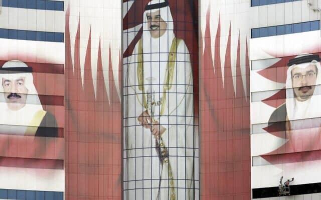 מגדל משרדים במנאמה, בחריין, הנושא את תמונתם של מלך בחריין, חמד בן עיסא אל-ח'ליפה, במרכז, ראש הממשלה ח'ליפה בן סלמאן אל-ח'ליפה, משמאל, ויורש העצר סלמאן בן אחמד אל-ח'ליפה, מימין, 3 באוקטובר 2011 (צילום: סוכנות הידיעות האמריקאית/חסן ג'מלי, ארכיון)