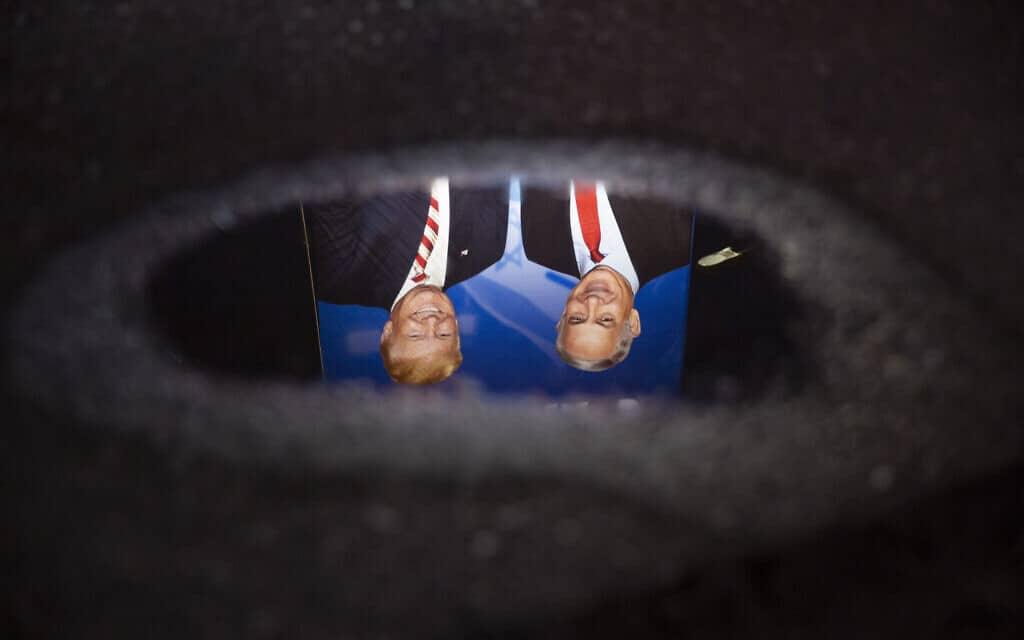 השתקפות שלט בחירות של נתניהו, בו הוא מופיע לצד טראמפ (צילום: AP Photo/Oded Balilty)