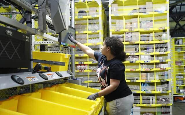 עובד ממיין פריטים במרכז של אמזון בניו יורק