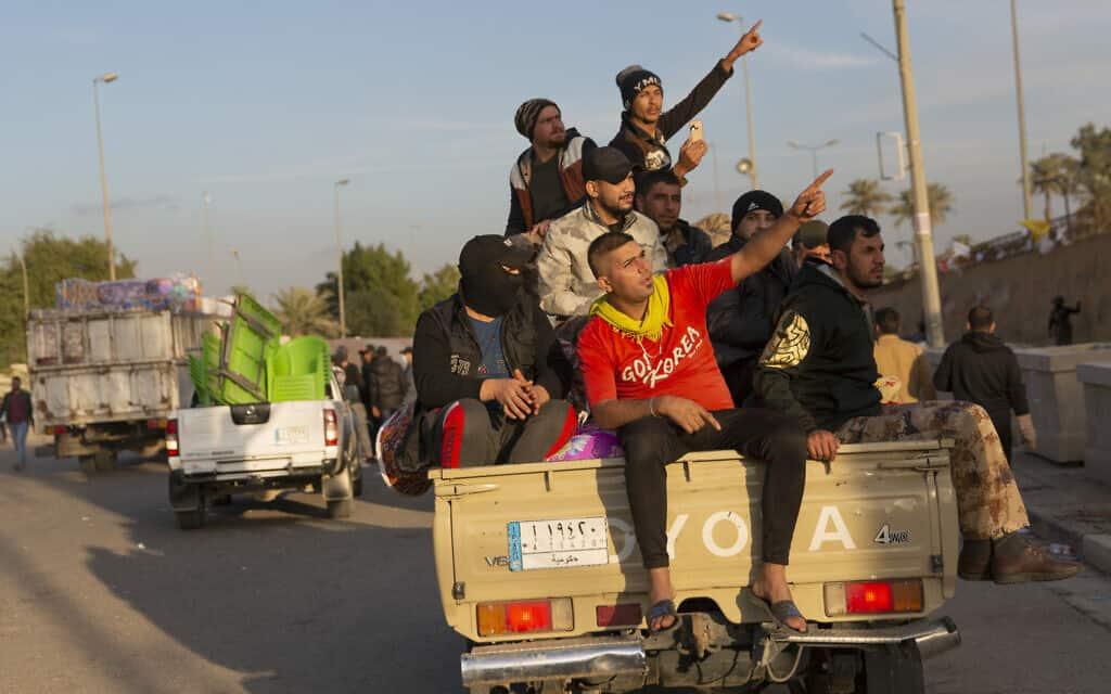 """מפגינים פרו-איראניים בדרכם חזרה מהמחאה ליד שגרירות ארה""""ב בעיראק (צילום: AP Photo/Nasser Nasser)"""