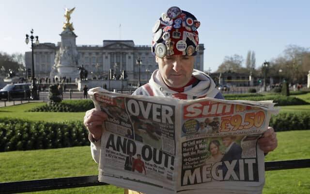 איש מוזר קורא את הסאן ביום ההודעה על מגזיט, על רקע ארמון באקינגהאם (צילום: AP Photo/Kirsty Wigglesworth)