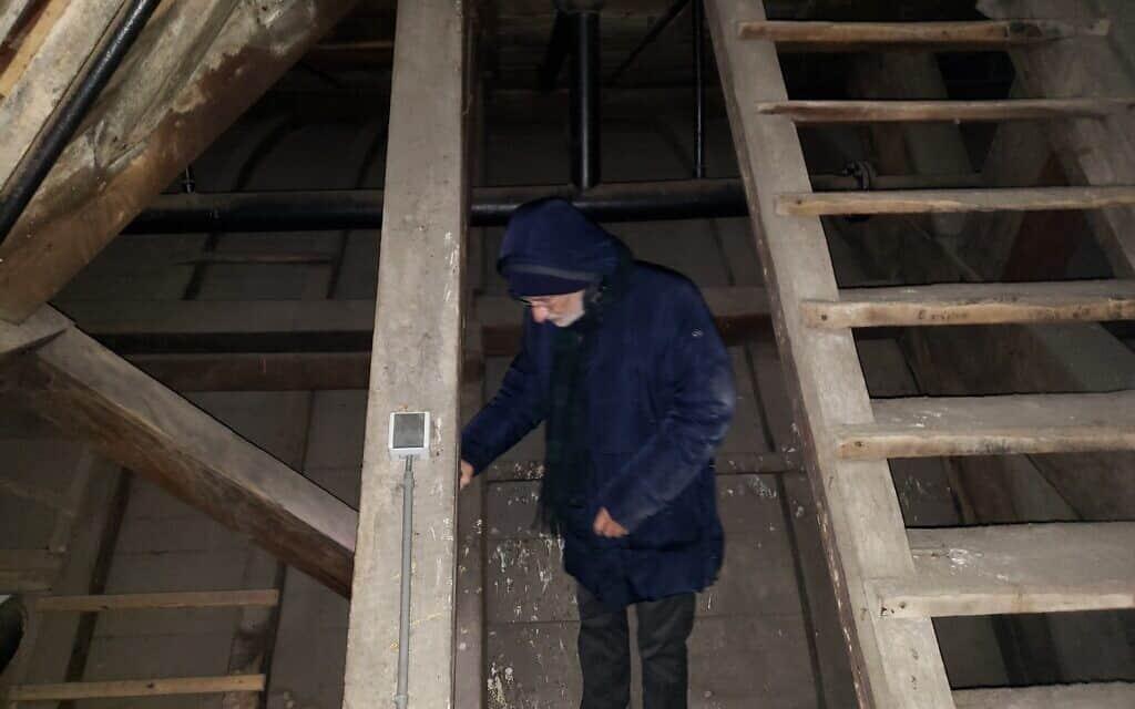 בראם פאלש בעליית הגג של בית הכנסת הפורטוגזי באמסטרדם, מתבונן בחלל שבו אביו, לוחם האש ליאו פאלש, החביא את אוצרות הקהילה היהודית מפני הנאצים, 25 בנובמבר 2019 (צילום: מאט ליבוביץ')