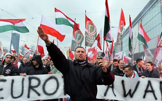 """מפגין צועק ומצדיע במועל יד לפני שלט עליו כתוב """"אירופה תתעוררי"""" (צילום: יאנק סקרינסקי\ AFP\ גטי אימג'ס דרך JTA)"""