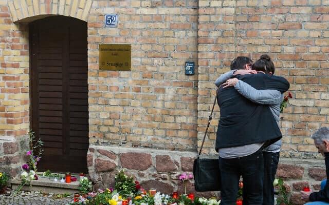 שני אזרחים גרמנים בחזית בית הכנסת בהאלה בגרמניה, יום לאחר המתקפה הרצחנית שאירעה בסמוך. 10 באוקטובר 2019 (צילום: (ינס שלואטר/Getty Images))