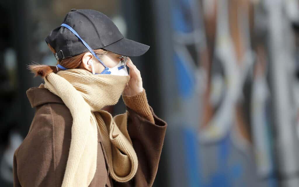 אישה עם מסיכת הגנה לפנים (צילום: AP Photo/Frank Augstein)