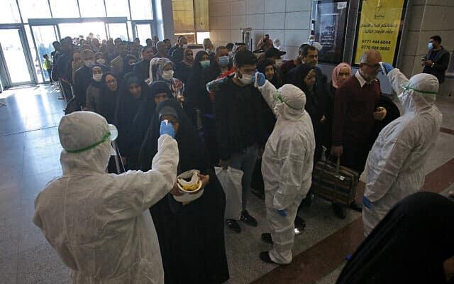 צוות רפואי בודק את הנוסעים המגיעים מאירן בשדה התעופה בעירק (צילום: AP Photo/Anmar Khalil, File)