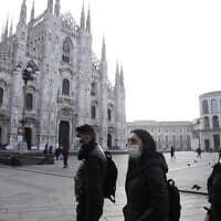 עוברי אורח עם מסיכות מגן על פניהם במילאנו שבאיטליה, 23 בפברואר 2020 (צילום: Luca Bruno, AP)
