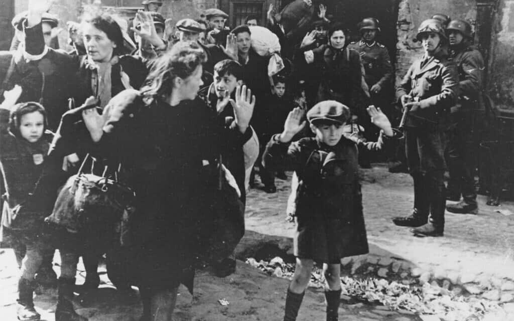 קבוצה של יהודים, ביניהם ילד קטן, מובלים מגטו ורשה על ידי חיילים גרמנים, 19 באפריל, 1943 (צילום: AP)