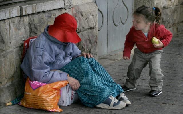 ילדה ישראלית מציצה אל חסרת בית היושבת על המדרכה (צילום: Orel Cohen/Flash90)