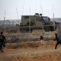 """פלסטינים מחד וכוח צה""""ל מאידך בגבול עזה-ישראל, ארכיון; למצולמים אין קשר לידיעה (צילום: Fadi Fahd/Flash90)"""