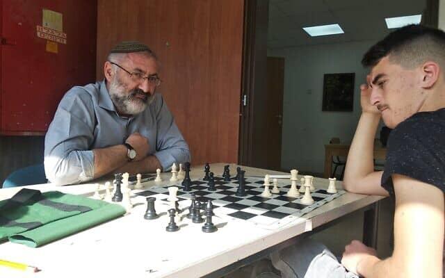 """מנחם לב, יו""""ר מחלקת חינוך בבית אל משחק שחמט עם תלמיד (צילום: Jacob Magid)"""