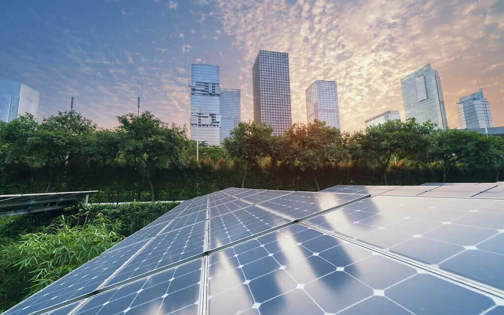 Solar Power Plant in modern city in sunset,Sustainable Renewable Energy (צילום: iStock-kynny)