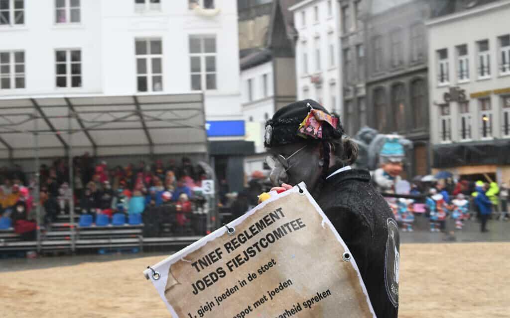 """גבר עם אף מלאכותי מעוקל, נושא שלט המזהיר, """"אסור לספר את האמת על היהודים"""" בתהלוכה השנתית של הקרנבל באלסט שבבלגיה, 23 בפברואר 2020 (צילום: כנען ליפשיץ)"""