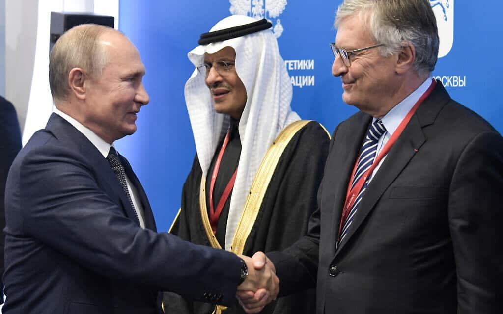 נשיא רוסיה ולדימיר פוטין לוחץ ידיים עם יו״ר מעצת האנרגיה העולמית ז׳ן-מארי דוגר. ביניהם, שר האנרגיה של סעודיה, עבדולעזיז בן סלמן (צילום: Alexei Nikolsky, Sputnik, Kremlin Pool Photo via AP)