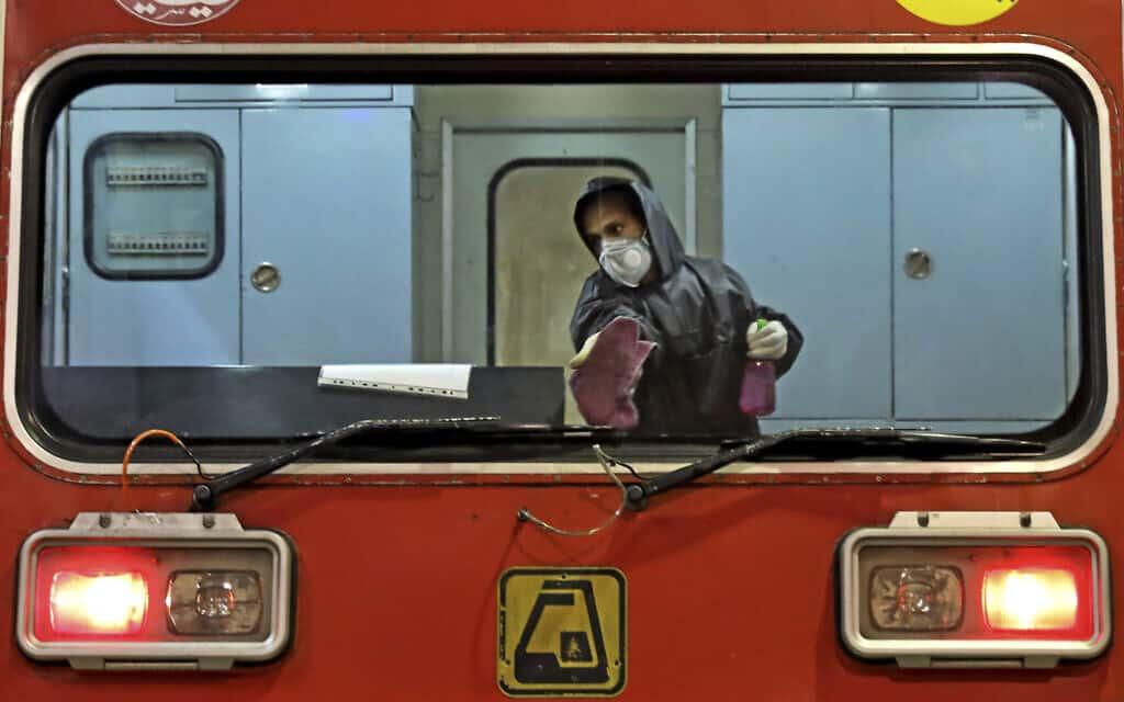 עובד חברת הרכבות האיראנית מחטא קרון מפני איום הקורונה (צילום: AP Photo/Ebrahim Noroozi)