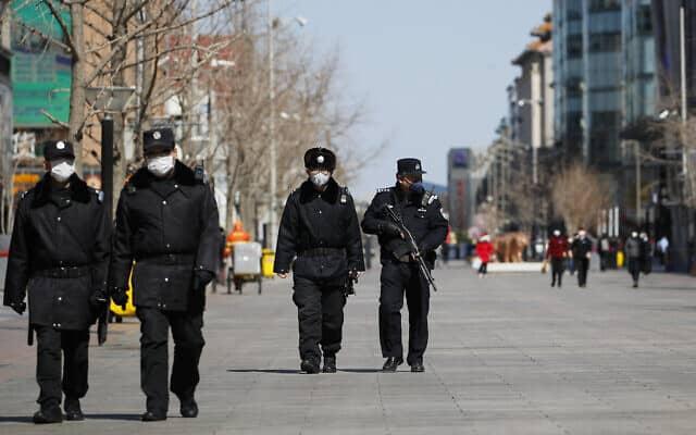 בהלת הקורונה: אנשי ביטחון במסיכות מפטרלים בסין, מרץ 2020 (צילום: AP Photo/Andy Wong)