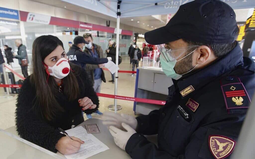 התפרצות הקורונה באיטליה: תושבים המבקשים להשתמש בתחבורה ציבורית נבדקים על ידי המשטרה מקומית וממלאים טפסים (צילום: AP Photo/Andrew Medichini)