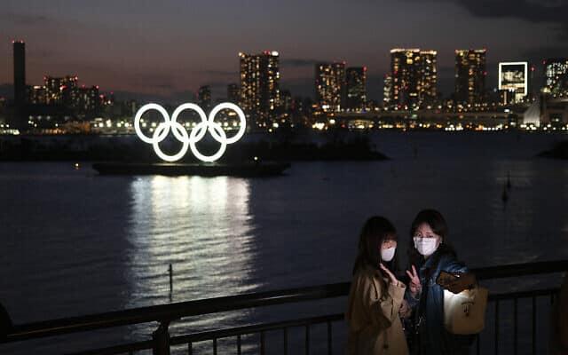 נשים מצטלמות על רקע הטבעות האולימפיות בטוקיו. מרץ 2020 (צילום: AP Photo/Jae C. Hong)