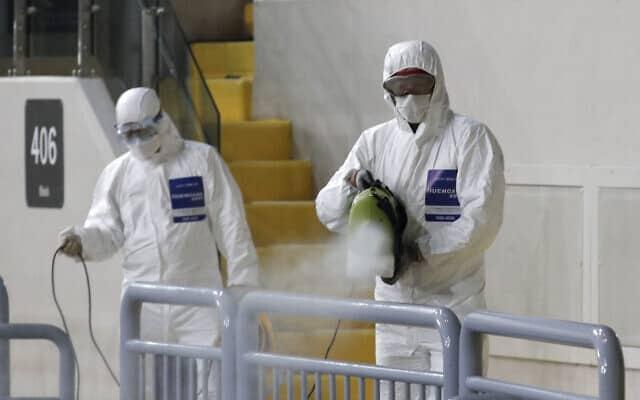 עובדים לובשים בגדי מגן מחטאים מרחבים ציבוריים נגד נגיף הקורונה בדרום קוריאה. במרץ 2020 (צילום: AP Photo/Lee Jin-man)