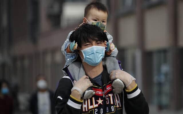 גבר נושא פעוט על כתפיו בבייג'ינג (צילום: (AP Photo/Andy Wong))