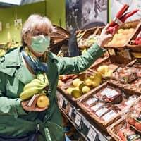 משבר הקורונה: אישה מבוגרת מצטיידת במזון בגרמניה, מרץ 2020 (צילום: AP Photo/Martin Meissner)