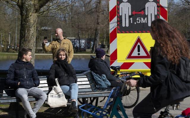 הולנדים מבלים ליד שלט הקורא להם לשמור מרחק זה מזה (צילום: AP Photo/Peter Dejong)