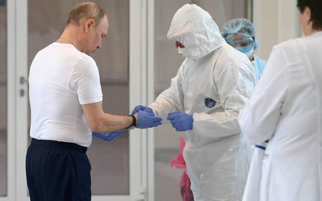 פוטין נערך לכניסה לבית חולים שבו שוהים חולי קורונה (Alexei Druzhinin, Sputnik, Kremlin Pool Photo via AP)