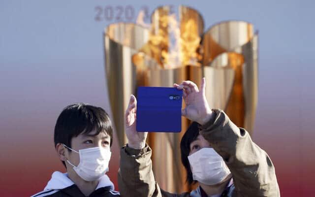 מבקרים מצטלמים על רקע הלפיד האולימפי בטוקיו. מרץ 2020 (צילום: AP Photo/Eugene Hoshiko)