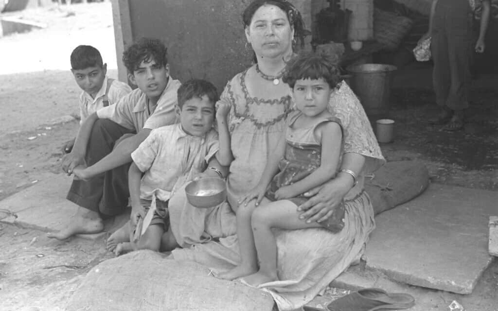 עולים חדשים בפתח ביתם במעברה בפרדס חנה. יוני 1946 (צילום: לע״מ)