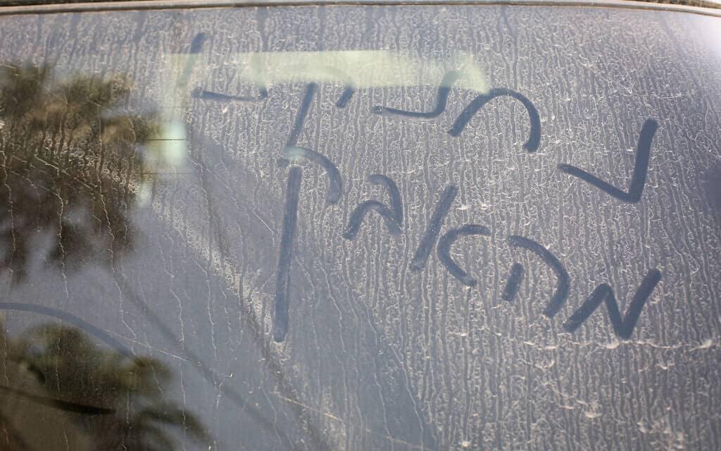 """""""נחנקנו מאבק"""" נכתב על שמשת מכונית מכוסה באבק, בעקבהות סופות חול, 2017 (צילום: דוד כהן/פלאש90)"""