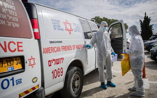 צוות רפואי עם לבוש מגן מפנה באמבולנס חולה עם חשד שנדבקה בקורונה (צילום: Yonatan Sindel/Flash90)