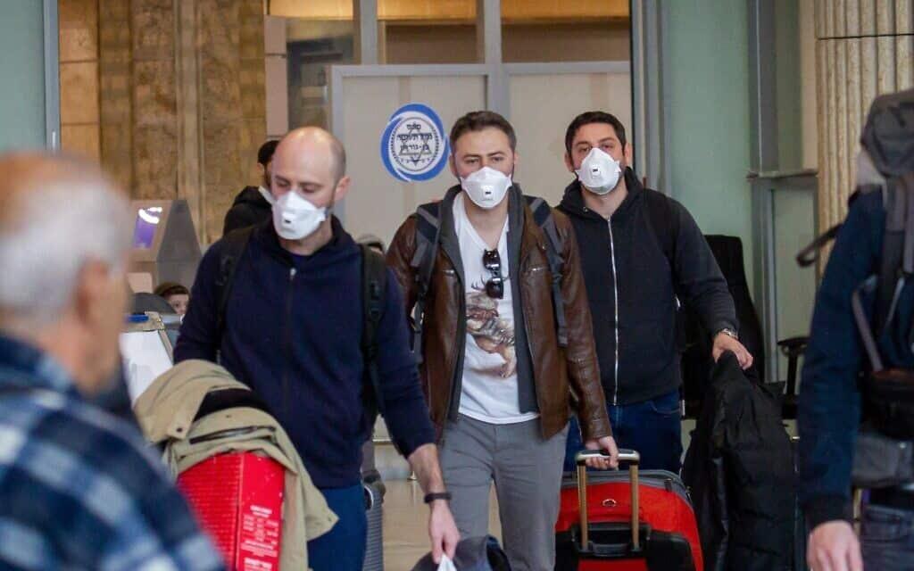 אנשים לובשים מסכות פנים מחשש להידבקות בנגיף הקורונה. נמל התעופה בן גוריון, פברואר 2020