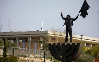 מפגינים מחוץ לכנסת מניפים ״דגל שחור לדמוקרטיה״ ב-23 במרץ 2020 (צילום: Olivier Fitoussi/Flash90)