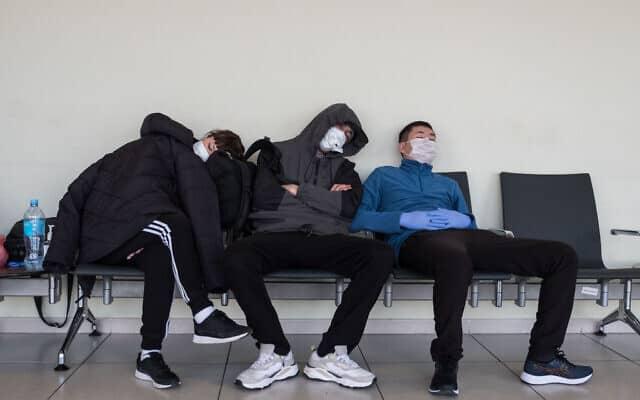 מטיילים לובשים מסכת פנים מחשש לנגיף הקורונה, בשדה התעופה במוסקבה ברוסיה (צילום: Noam Revkin Fenton/Flash90)