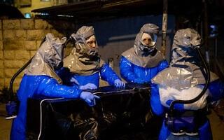 עובדי חברת קדישא לובשים בגדי מגן (צילום: Yonatan Sindel/Flash90)