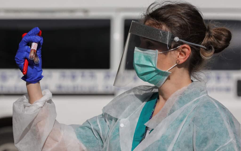 עובדת בצוות הרפואי בבית חולים הדסה עין כרם עם דגימת בדיקה לאבחון וירוס הקורונה. 26 במרץ 2020 (צילום: Olivier Fitoussi/Flash90)