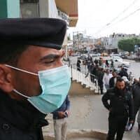 שוטר פלסטיני עם מסיכת הגנה, שומר על הסדר בתור לקבלת כספי הסיוע הקטארי מסניף דואר ברפיח בדרום רצועת עזה. 31 במרץ 2020 (צילום: Abed Rahim Khatib/ Flash90)