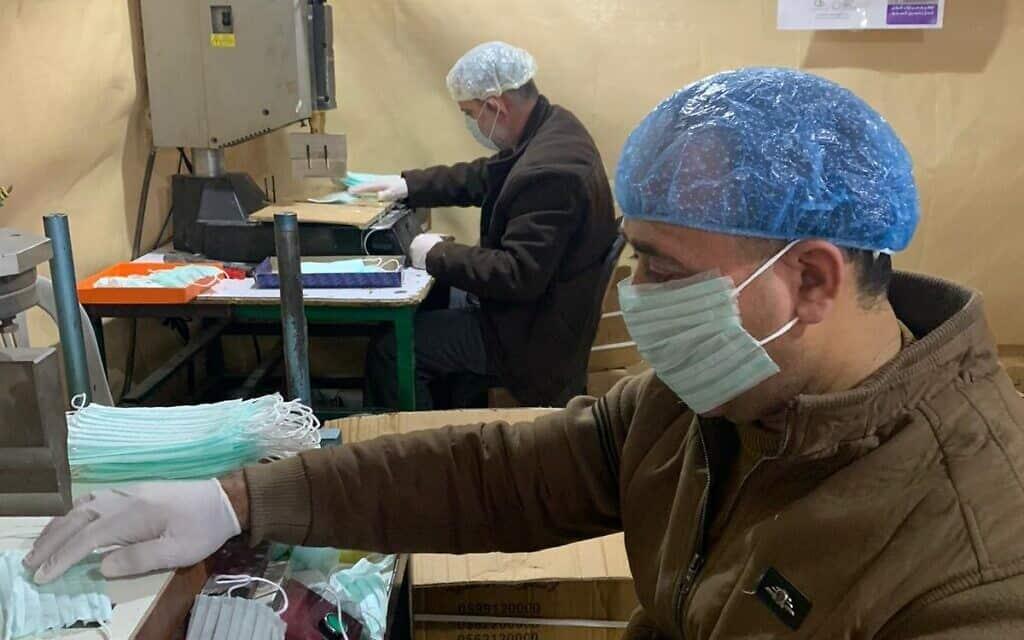 פועלים במפעל בחברון מייצרים מסכות (צילום: באדיבות אחמד זוע'ייר)